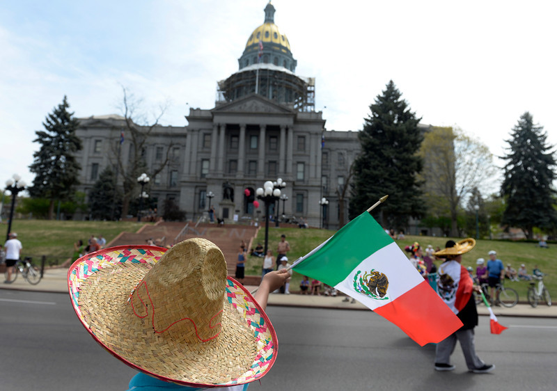 """. Crowds wearing sombreros and waving Mexican flags watch the parade in front of the state capitol. The 27th Annual Cinco de Mayo Festival kicks off with the \""""Celebrate Culture\"""" parade winding through downtown Denver and ending at the festival site in Civic Center Park. The event includes a green chile bowl cook off, a taco eating contest, chihuahua races, as well as cultural foods and musical and dance performances running through Sunday. (Kathryn Scott Osler, The Denver Post)"""