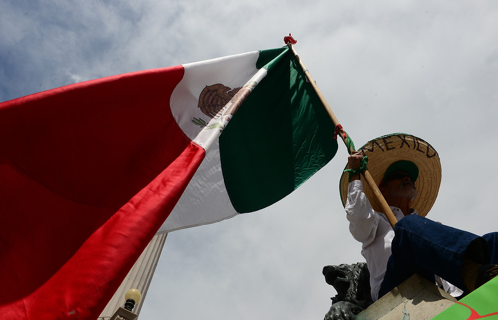 . Pedro Rodriguez holds up a large Mexican flag as he listens to Mexican music during the Cinco de Mayo celebrations at Civic Center Park in Denver, CO on May 24 2014. (Photo By Helen H. Richardson/ The Denver Post)