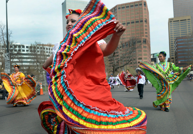 """. Dressed in colorful costumes, members of the Colorado Mestizo Dancers make their way down Lincoln Street in front of the state capitol. The 27th Annual Cinco de Mayo Festival kicks off with the \""""Celebrate Culture\"""" parade winding through downtown Denver and ending at the festival site in Civic Center Park. The event includes a green chile bowl cook off, a taco eating contest, chihuahua races, as well as cultural foods and musical and dance performances running through Sunday. (Kathryn Scott Osler, The Denver Post)"""