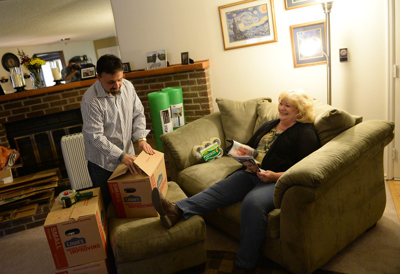 . Columbine High School Principal Frank DeAngelis, left, backs boxes, at his home in Thornton, as his fiancee Diane Meyer, relaxes for a bit after getting home, May 02, 2014. DeAngelis plans to retire at the end of the school year and they are getting ready to put their home on the market. The two are building a new home in Arvada where they plan to live when they retire. (Photo by RJ Sangosti/The Denver Post)