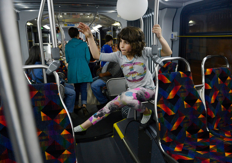 . Leah Folsom, 6, takes advantage of the new RTD Free MetroRide bus, by climbing it\'s rails that was parked the underground bus concourse during the grand opening of the Union Station Transit Center Friday morning, May 09, 2014. (Photo By Andy Cross / The Denver Post)