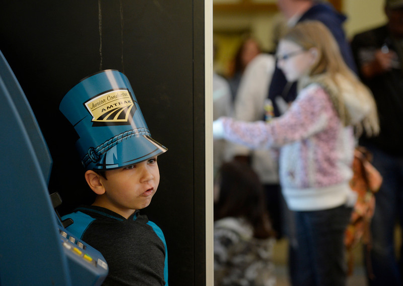 . Gabriel Nuno, 5, stands by and watches the crowd walk through a section of Union Station, the Amtrak ticket office, during the grand opening of the Union Station Transit Center Friday morning, May 09, 2014. (Photo By Andy Cross / The Denver Post)
