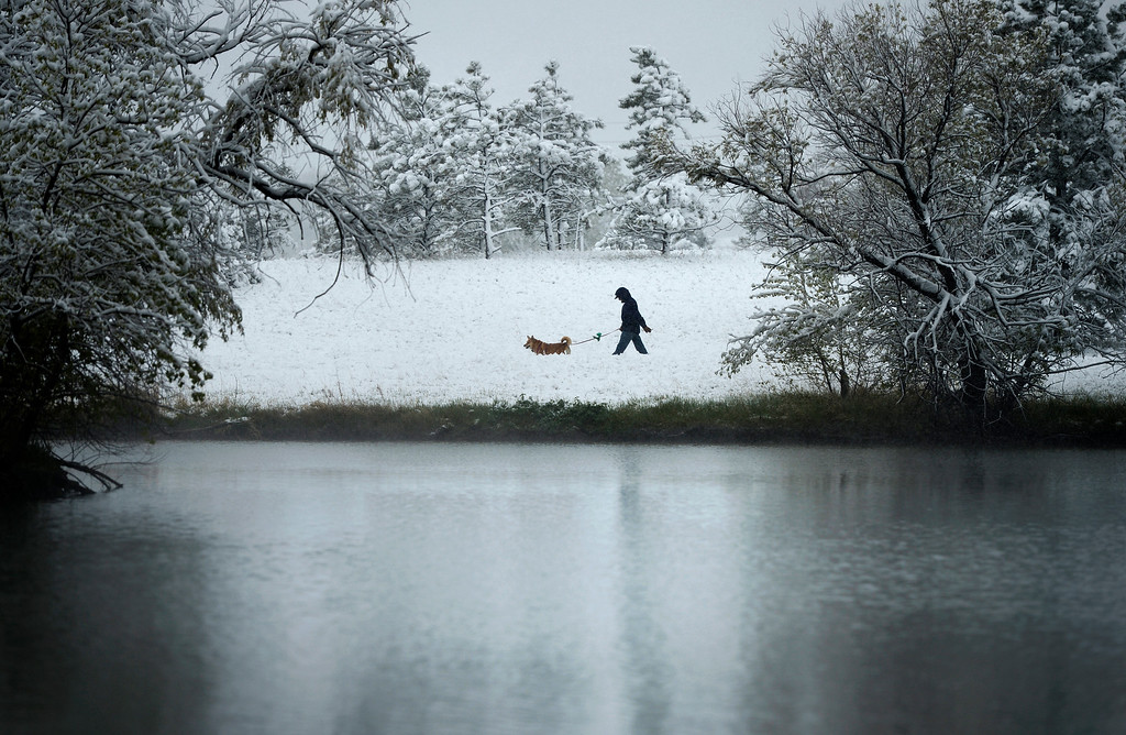 . A man takes his dog for a morning walk in Belmar Park in Lakewood, May 12, 2014. A slow moving spring snow storm has blanketed much of the Denver area in new snow. (Photo by RJ Sangosti/The Denver Post)