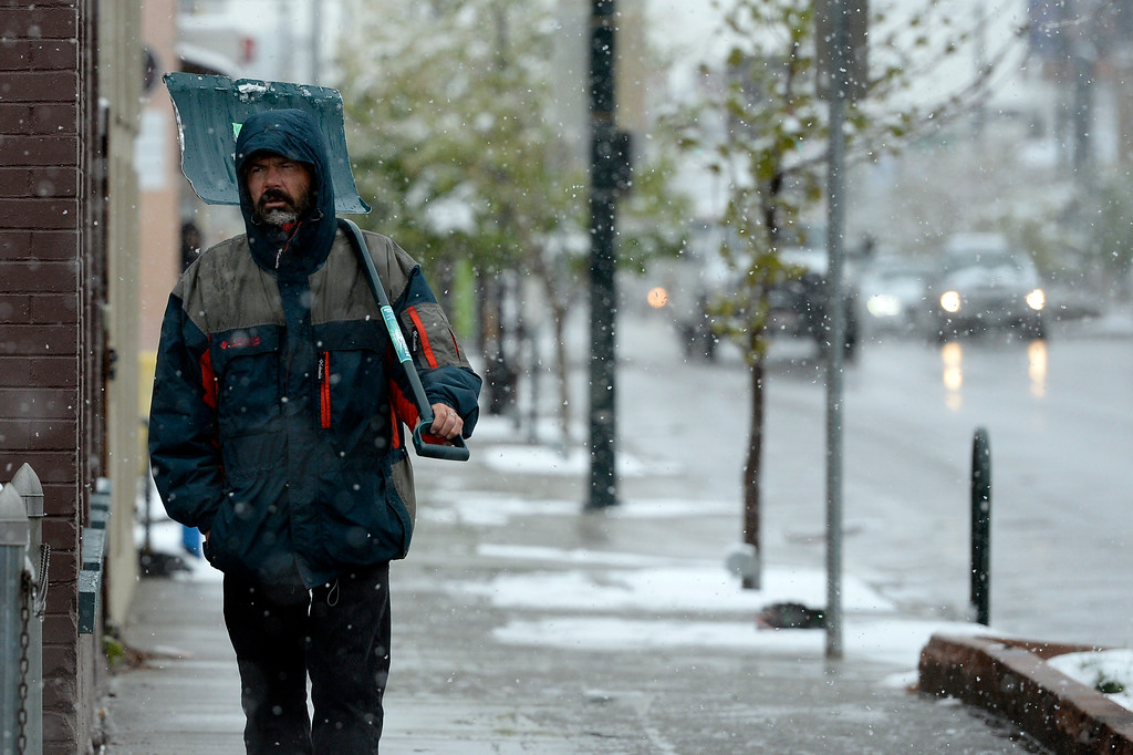 . Snow hit the Denver metro area on Monday, May 12, 2014.  Danny Evans walks down S. Broadway in Denver with his shovel ready to clear sidewalks. (Denver Post Photo by Cyrus McCrimmon)