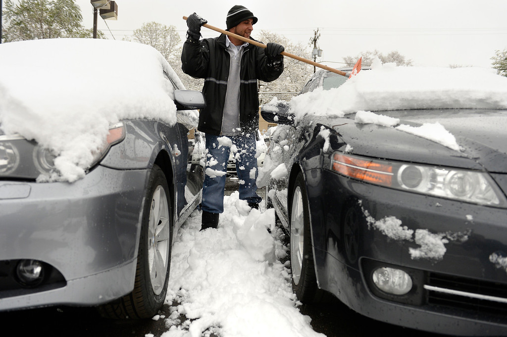. Snow hit the Denver metro area on Monday, May 12, 2014.   Ahsan Khelik clears cars at Royal Automotive  on S. Broadway in Englewood, CO. (Denver Post Photo by Cyrus McCrimmon)
