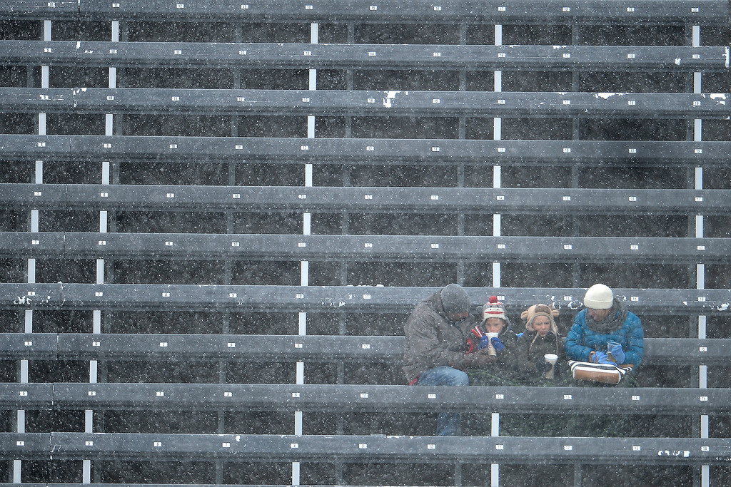 . A family huddles in the stands as snow falls and the wind gusts during the first half. The Colorado Rapids host Chivas U.S.A. on Sunday, May 11, 2014. (Photo by AAron Ontiveroz/The Denver Post)
