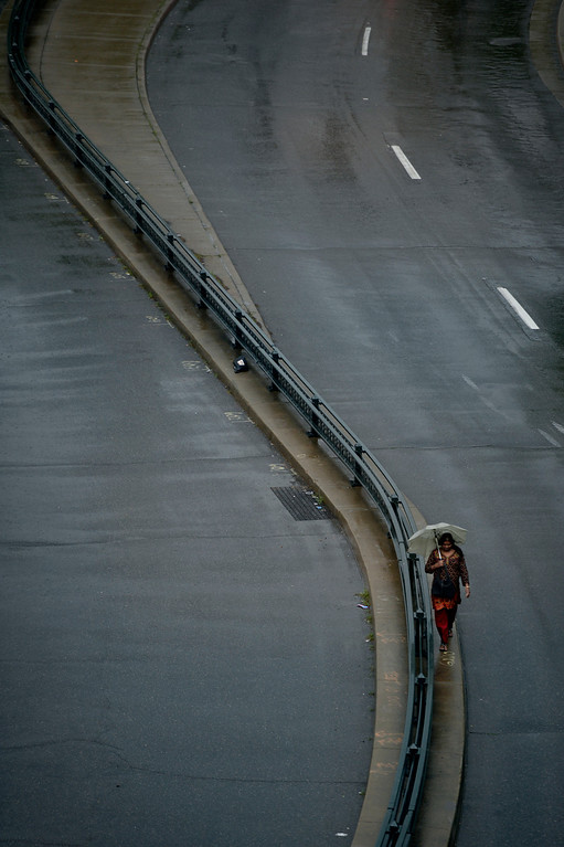 . A woman passes along Colfax Ave during afternoon rain in Denver, CO May 22, 2014. Heavy rain and hail pelted the Front Range on Thursday, the third consecutive day of severe storms. (Photo By Craig F. Walker / The Denver Post)