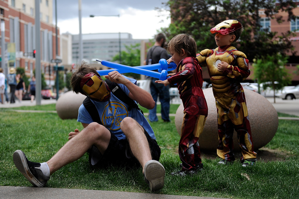 . Dewey Pruitt gets attacked with balloon swords by his sons Corben, 5, and Ronin, 4, as they play outside during Denver Comic Con at the Colorado Convention Center in Denver, Colorado on June 14, 2014. (Photo by Seth McConnell/The Denver Post)