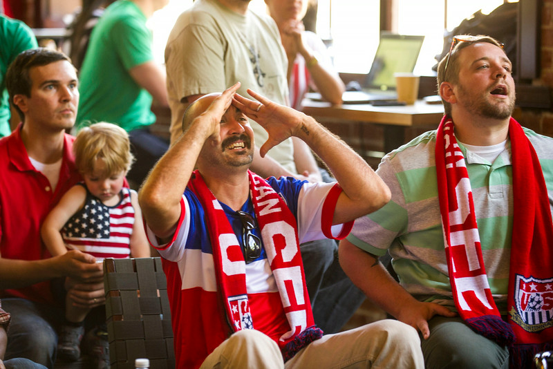 . Nache Greene (center) and Luke Warner (right), both of Denver, react while watching a World Cup game between the United States and Germany in a common area at Gather, a cafe and lounge that shares a space with Galvinate, a digital startup hub, on Thursday, June 26, 2014 in Denver, CO.  Despite losing 0-1 to Germany, the United States advances to round 16. (Photo By Kent Nishimura/The Denver Post)
