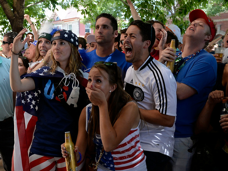. Ally Goodman and Callie Pote react to Germany\'s goal int he second half as Germany Fan Jon Massopust celebrates. Fans gathered outside on the sidewalk at The Three Lions Pub on Colfax and York St. June 26, 2014 to watch the US play Germany in World Cup competition in Recife.  (Photo by John Leyba/The Denver Post)