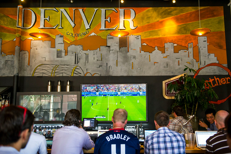 . People gather in a common area to watch the world cup, some with their laptops, at Gather, a cafe and lounge that shares a space with Galvinate, a digital startup hub on Thursday, June 26, 2014 in Denver, CO.  Despite losing 0-1 to Germany, the United States advances to round 16. (Photo By Kent Nishimura/The Denver Post)