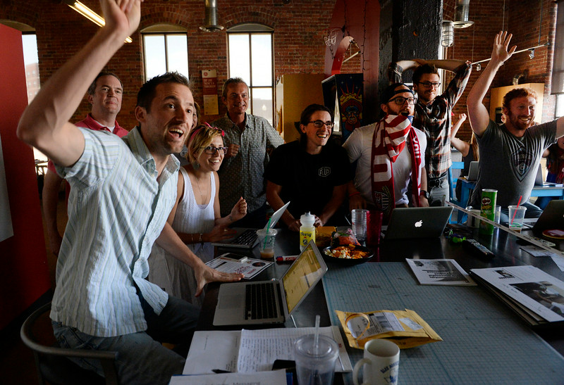 . Employees of the Amelie Company, an advertising and PR firm in lower downtown Denver, celebrate a late flurry of action as the USA soccer team played Germany in the 2014 World Cup, June 26, 2014. USA lost 1-0, but still advance in the tournament because Ghana lost to Portugal. (Photo By Andy Cross / The Denver Post)