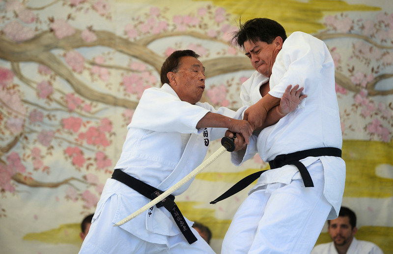. Seiji Tanaka, left, and Antonio Cano, members of the Hyland Hills Aikido club demonstrate Katana sword technique on stage during the annual Cherry Blossom Festival at the Sakura Square Saturday afternoon, June 28, 2014. The festival, which runs through Sunday 11-4 pm, showcases the Japanese American Culture that includes traditional dances, music, various demonstrations, and food. (Photo By Andy Cross / The Denver Post)