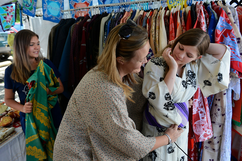 . Mira Killmeyer, center, with Vintage Kimono, fits Jazzalyn Marsh, 12, from Pueblo Colorado, right, with a sash around a traditional Kimono in a booth set up at the annual Cherry Blossom Festival at the Sakura Square Saturday afternoon, June 28, 2014. Jazzalyn\'s sister, Janaya, left, 13, waits to get fitted. The festival, which runs through Sunday 11-4 pm, showcases the Japanese American Culture that includes traditional dances, music, various demonstrations, and food.(Photo By Andy Cross / The Denver Post)
