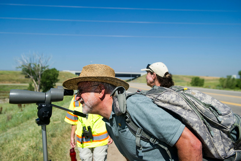 . Raptor Education Foundation director Peter Reshetniak peers through a spotting scope pointed at a female eaglet that is expected to take tis first flight soon, along E120th Avenue near, E-470 where an eagles nest is located on Thursday, July 03, 2014 in Commerce City, CO.  Volunteers  rotate in shifts to keep watch over the baby eagle, as it is expected to take flight soon, and it\'s nests proximity to E-470 tollway is worrisome. (Photo by Kent Nishimura/The Denver Post)