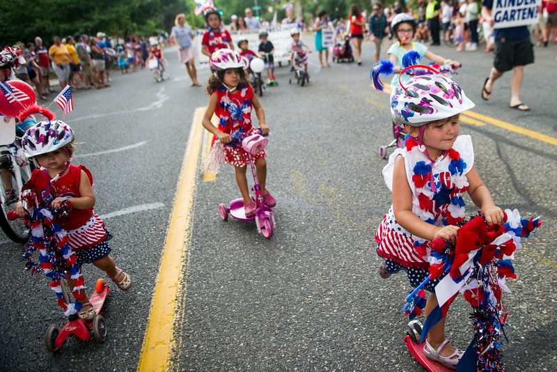 . Divienne Hoppe, 4, and other children from the Pattington Station Preschool ride scooters and bikes for the 5th Annual July 4th Park Hill Parade along 23rd Avenue  on Friday, July 04, 2014 in Denver, CO.  The parade, which ran from Dexter Street to Krameria Street, featured marchers, marching bands, bikers, floats and classic cars.  (Photo by Kent Nishimura/The Denver Post)