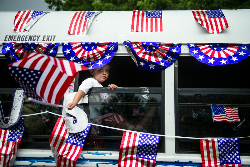 . Brooke Bentley, 3, waves and American flag out the window of the Park Hill Children\'s Center bus which was a part of the 5th Annual July 4th Park Hill Parade along 23rd Avenue  on Friday, July 04, 2014 in Denver, CO.  The parade, which ran from Dexter Street to Krameria Street, featured marchers, marching bands, bikers, floats and classic cars.  (Photo by Kent Nishimura/The Denver Post)