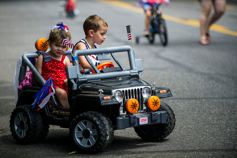 . Braxton Nava, 4, and Leilani Nava, 2, ride in a battery powered children\'s jeep on 23rd Avenue after the 5th Annual July 4th Park Hill Parade along 23rd Avenue  on Friday, July 04, 2014 in Denver, CO.  The parade, which ran from Dexter Street to Krameria Street, featured marchers, marching bands, bikers, floats and classic cars.  (Photo by Kent Nishimura/The Denver Post)