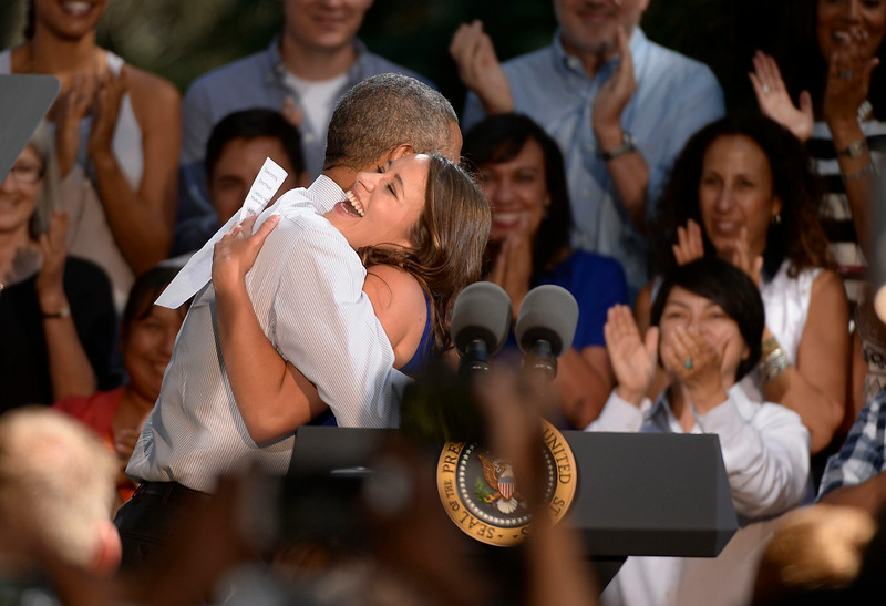 . Alex Dooley, who lives in Denver and works at a furniture upholstery store gets a hug from President Obama after introducing him to the guests. President Obama spoke to a crowd of hand-picked guests at Cheesman Park July 9, 2014 in Denver. Obama next headed to raise money for U.S. Sen. Mark Udall\'s re-election campaign at a private luncheon at the Westin Denver Downtown hotel. (Photo by John Leyba/The Denver Post)