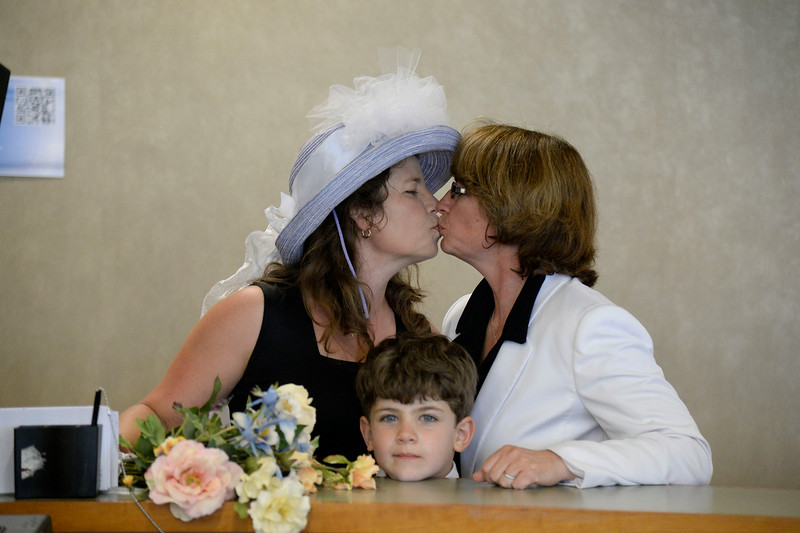. Anna Simon (L) and Fran Simon share a kiss as son Jeremy stands in the middle,  at the counter to get their license at the Denver County clerk\'s office where they began issuing same sex marriage licenses July 10, 2014. They are the first official married couple  as they self-solemnized at the office. They are the first to go on record with the Denver County clerk\'s office. (Photo by John Leyba/The Denver Post)