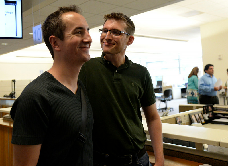 . Jason Woodrich (R) and Ben Hauth were all smiles after receiving their marriage license at the Denver County clerk\'s office where they began issuing same sex marriage licenses July 10, 2014. They are the first official male couple to get married. (Photo by John Leyba/The Denver Post)
