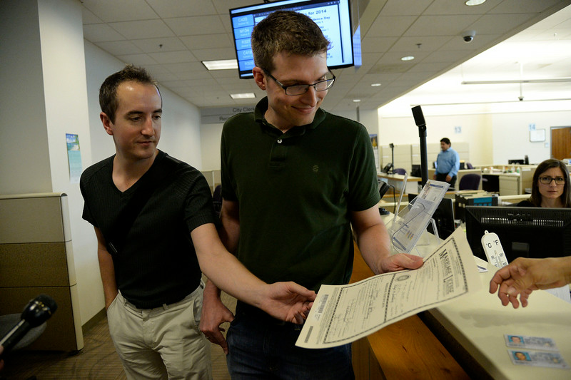 . Ben Hauth (L) and Jason Woodrich receive their marriage license at the Denver County clerk\'s office where they began issuing same sex marriage licenses July 10, 2014. They are the first official male couple to get married. (Photo by John Leyba/The Denver Post)