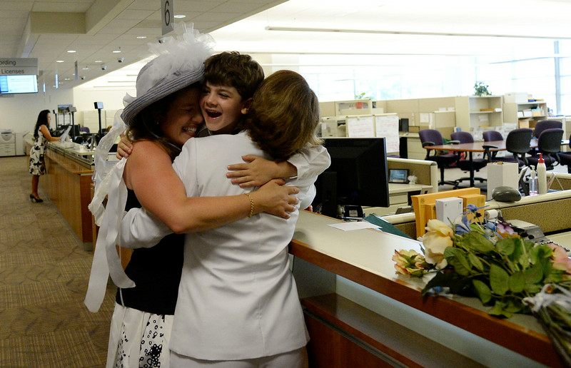 . Anna Simon (L) and Fran Simon hug their son Jeremy after it was official, the first same sex married couple to get their license at the Denver County clerk\'s office where they began issuing same sex marriage licenses July 10, 2014. (Photo by John Leyba/The Denver Post)