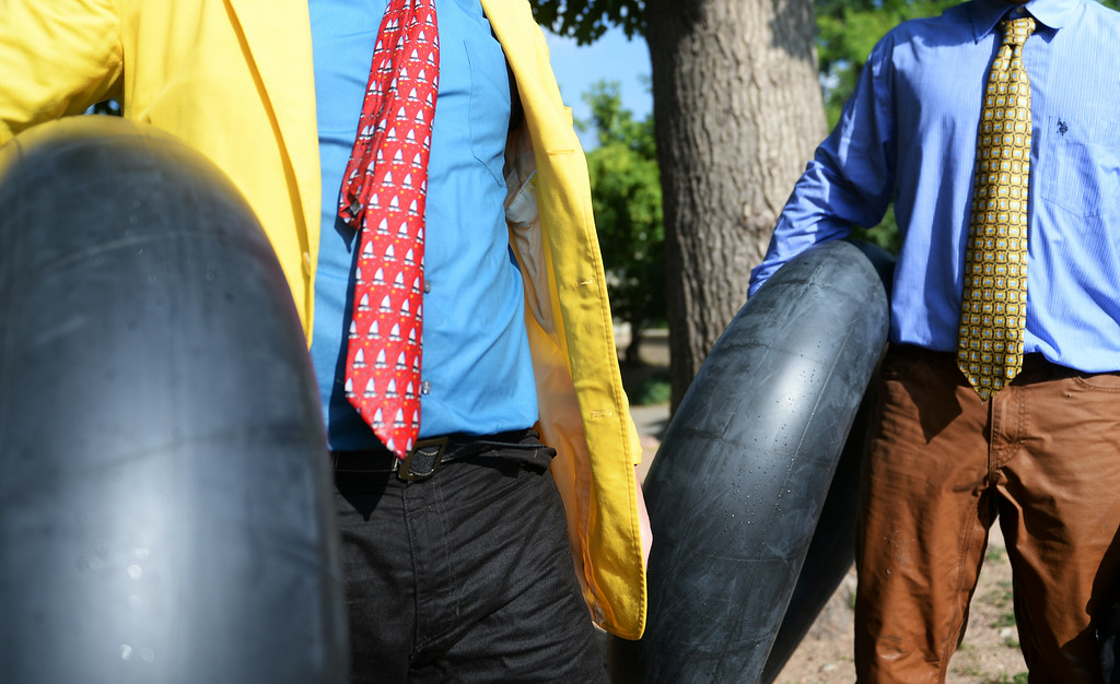 . Tim Laramy, left, and Jack Craig dressed in ties carry their tubes as they finish riding Boulder Creek during Boulder\'s Tube to Work Day, July 15, 2014. Around 40 participants took their tubes down Boulder Creek on their way to work. (Photo by RJ Sangosti/The Denver Post)