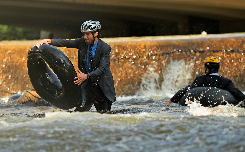 . Quayle Hodek, dressed in a suit and tie, hops back on his tube during Boulder\'s Tube to Work Day, July 15, 2014. Around 40 participants took their tubes down Boulder Creek on their way to work. (Photo by RJ Sangosti/The Denver Post)