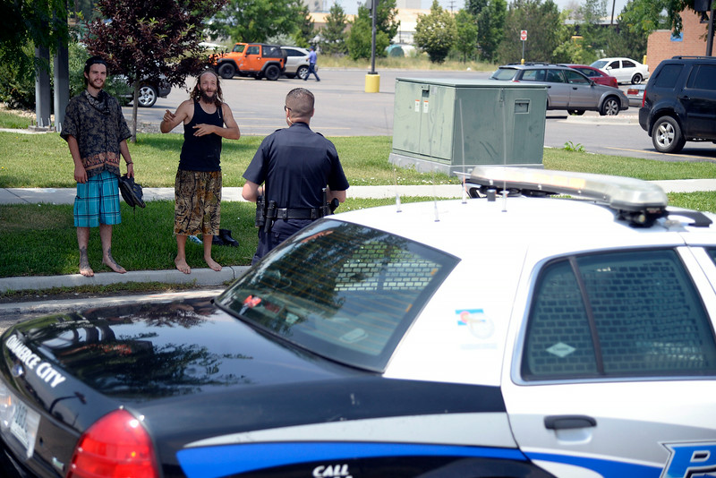 """. Jeffrey \""""Gator\"""" Harris (tank top) and Josh Bearden ask Commerce City police offers JW Jenkins for directions to an auto salvage company. (Photo by AAron Ontiveroz/The Denver Post)"""
