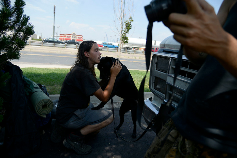 . Kameron Kolding embraces on of his family\'s multiple dogs as they try to overcome an obstacle of low finances and the need for automobile repair. (Photo by AAron Ontiveroz/The Denver Post)