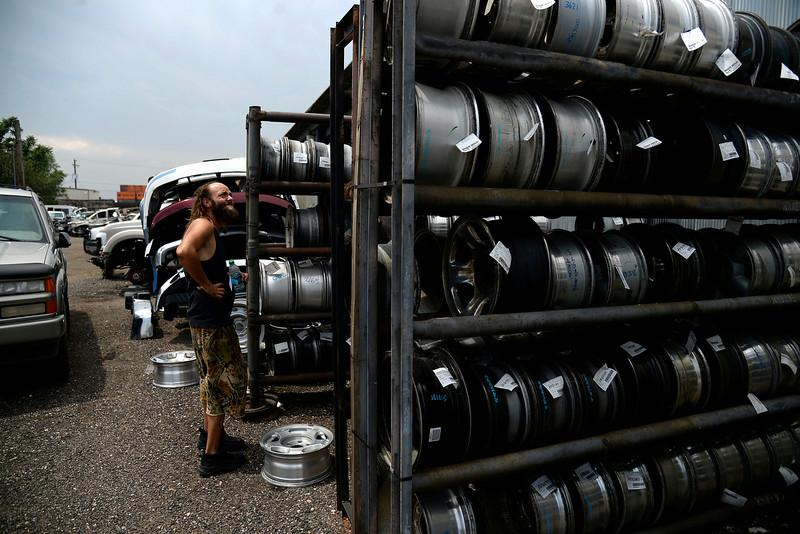 """. Jeffrey \""""Gator\"""" Harris looks at a stack of rims at Boot Hill Truck. Despite finding the rim he needed, Harris was unable to barter the three rims in his possession for the one he needed and thus set out on foot formulating a plan to finagle the rim. (Photo by AAron Ontiveroz/The Denver Post)"""