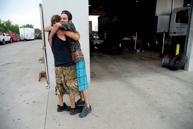 """. Josh Bearden (right) hugs Jeffrey \""""Gator\"""" Harris after a long couple days of getting their broken down van back on the road despite a lack of funds. The pair spent the day on foot with little cash hoping to get a new rim and tire, which they were able to do. (Photo by AAron Ontiveroz/The Denver Post)"""