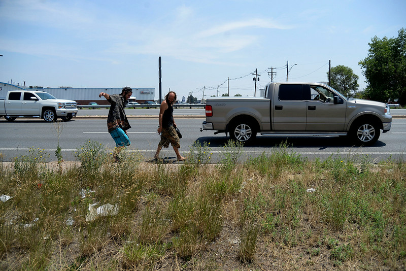 """. Jeffrey \""""Gator\"""" Harris and Josh Bearden set out barefoot along Vasquez Boulevard in search of a rim for their badly-damaged Chevy Van as it sits in limbo -- it is to be towed in less than 24 hours from a nearby WalMart. (Photo by AAron Ontiveroz/The Denver Post)"""