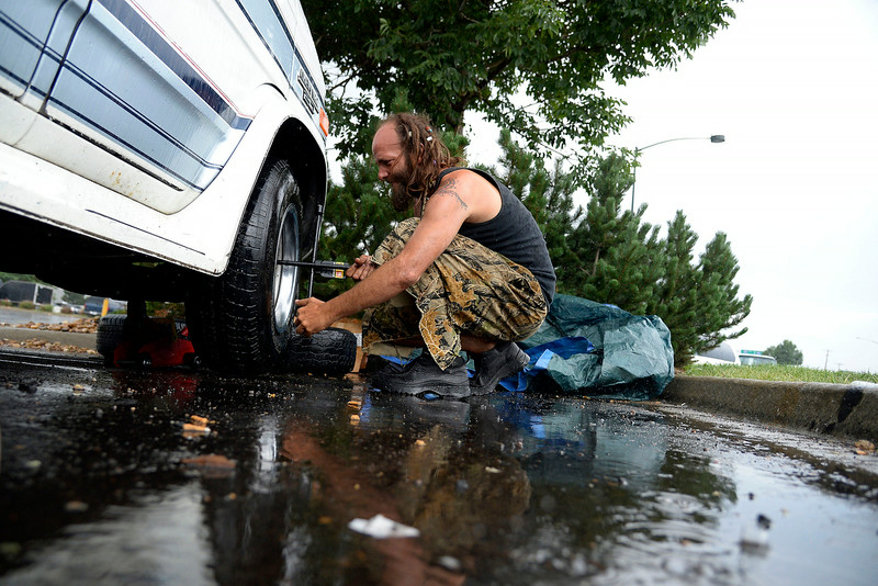 . As the rain begins to pour, Gator makes the last turns of the lug nut to secure his new rim. (Photo by AAron Ontiveroz/The Denver Post)