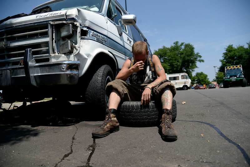 . Bugg (who provided no legal name) sits in front of his de facto family\'s Chevy van, which was badly damaged and in need of a new rim. (Photo by AAron Ontiveroz/The Denver Post)