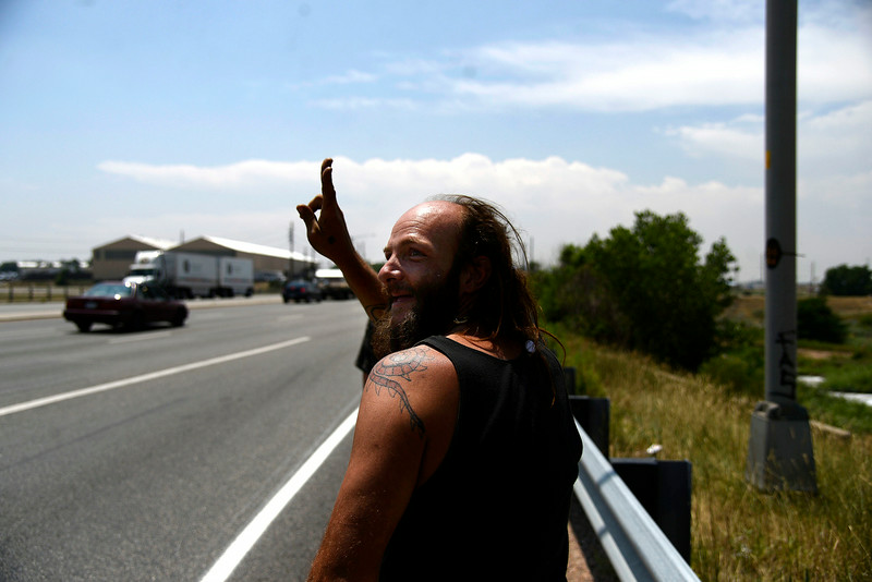 """. Jeffrey \""""Gator\"""" Harris offers a peace sign to oncoming traffic -- only one of four passing vehicles returned his gesture -- as he walks along Vasquez. (Photo by AAron Ontiveroz/The Denver Post)"""