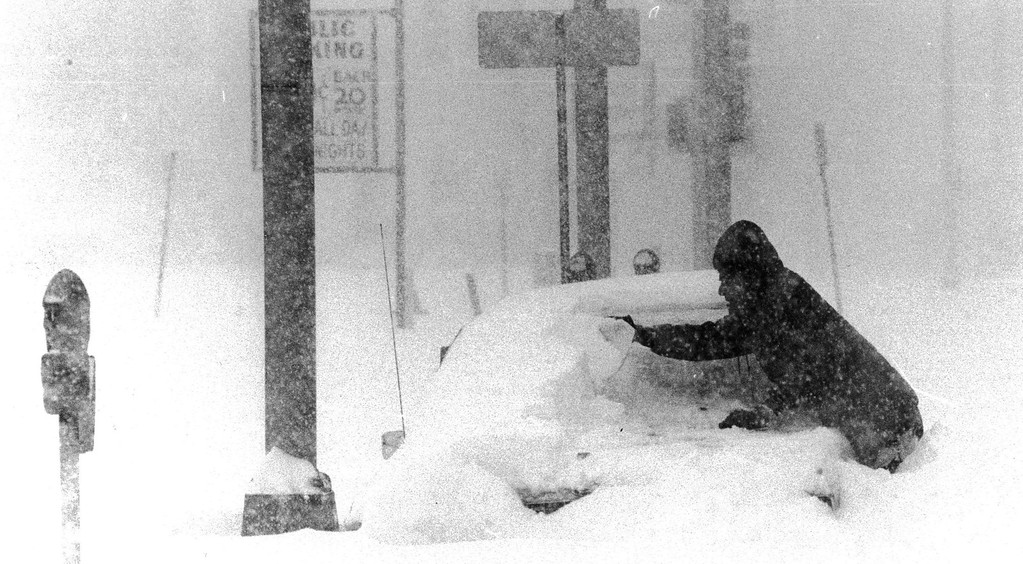 . A man trying to clear off a car during the Blizzard of \'82. Denver Post Library Archive