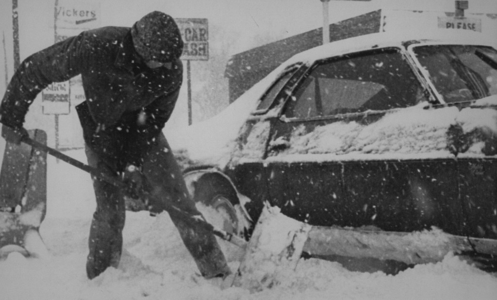 . Digging Out - A motorist uses a snow shovel to clear snow from under his automobile on Friday in Denver where more than a foot of snow blanketed the city. 1982. Credit: AP Laserphoto. Denver Post Library Archive