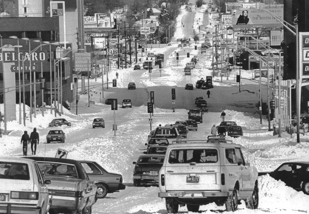 . Pedestrians seem to make as much progress through snow bound main street than autos which are spun out in various directions. A Christmas blizzard dumped up to three feet of snow. This scene was on Colorado Blvd in 1982. Credit: UPI  Denver Post Library Archive