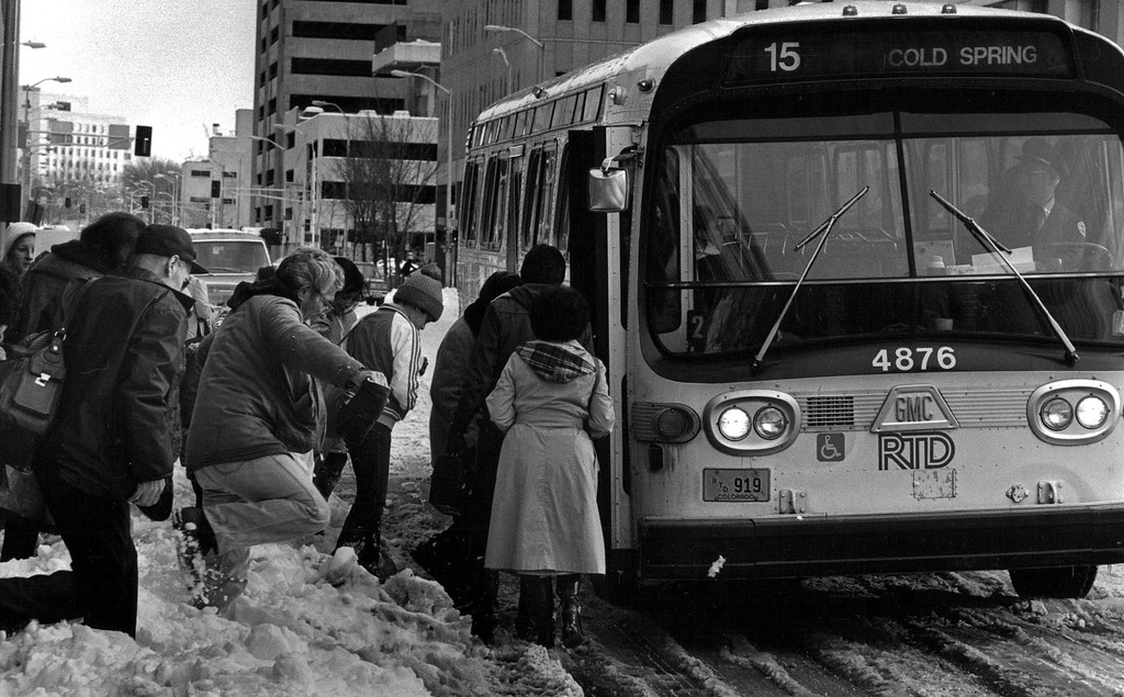 . People make their way over the snowbank to catch the bus after the Blizzard of \'82. Dave Buresh,  The Denver Post