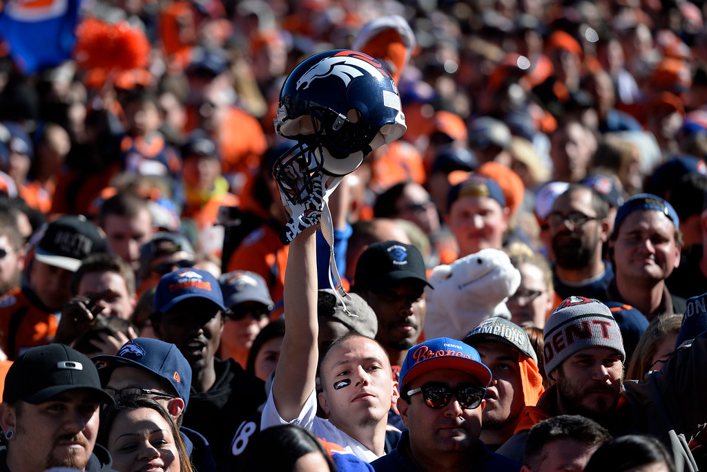 . David Sandoval holds a Broncos helmet high during the Denver Broncos Super Bowl championship celebration and parade on Tuesday February 9, 2016. (Photo By AAron Ontiveroz/The Denver Post)