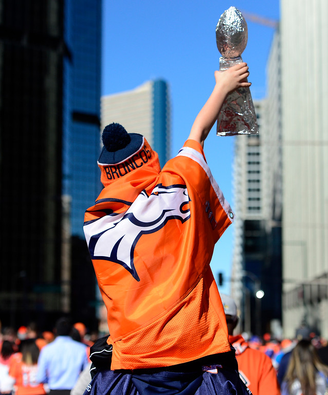 . DENVER, CO - FEBRUARY 9: Matthew Jayne raises his Lombardi trophy made out of aluminum foil abouve the crowd while leaving downtown on February 9, 2016 in Denver, Colorado. Fans gathered to celebrate the Denver Broncos\' Super Bowl win with a parade and a rally in Civic Center Park. (Photo by Brent Lewis/The Denver Post)
