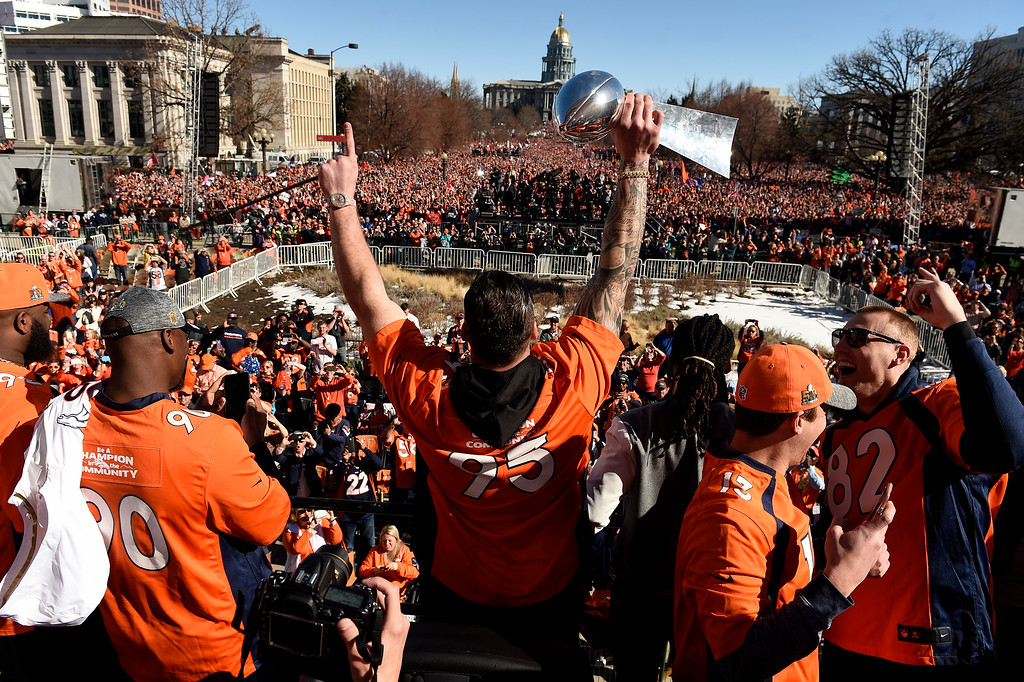 . Denver Broncos defensive end Derek Wolfe #95 holds the Lombardi Trophy over his head as he looks over a massive crowd during the Broncos Super Bowl rally at Civic Center  on February 9, 2016 in Denver, Colorado.   (Photo by Helen H. Richardson/The Denver Post)