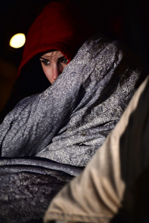 . Taylor Worthington, of Denver, tries to stay warm against the cold and wind as people begin to gather for the 67th annual Easter sunrise service at Red Rocks Amphitheater in Morrison, Colorado, on April 17, 2014. The popular annual event, which hosts thousands of worshipers, is sponsored by the Colorado Council of Churches.  (Photo By Helen H. Richardson/ The Denver Post)