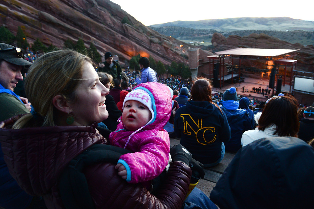 """. Jana Lomax holds her 10 month old daughter Althea while they and her husband Spencer, left, enjoy  the 67th annual Easter sunrise service  at Red Rocks Amphitheater in Morrison, Colorado, on April 17, 2014.  Superintendent Patrick L. Demmer gave the sermon which was entitled \""""What are you looking for?\"""".  The popular annual event, which hosts thousands of worshipers, is sponsored by the Colorado Council of Churches.  (Photo By Helen H. Richardson/ The Denver Post)"""