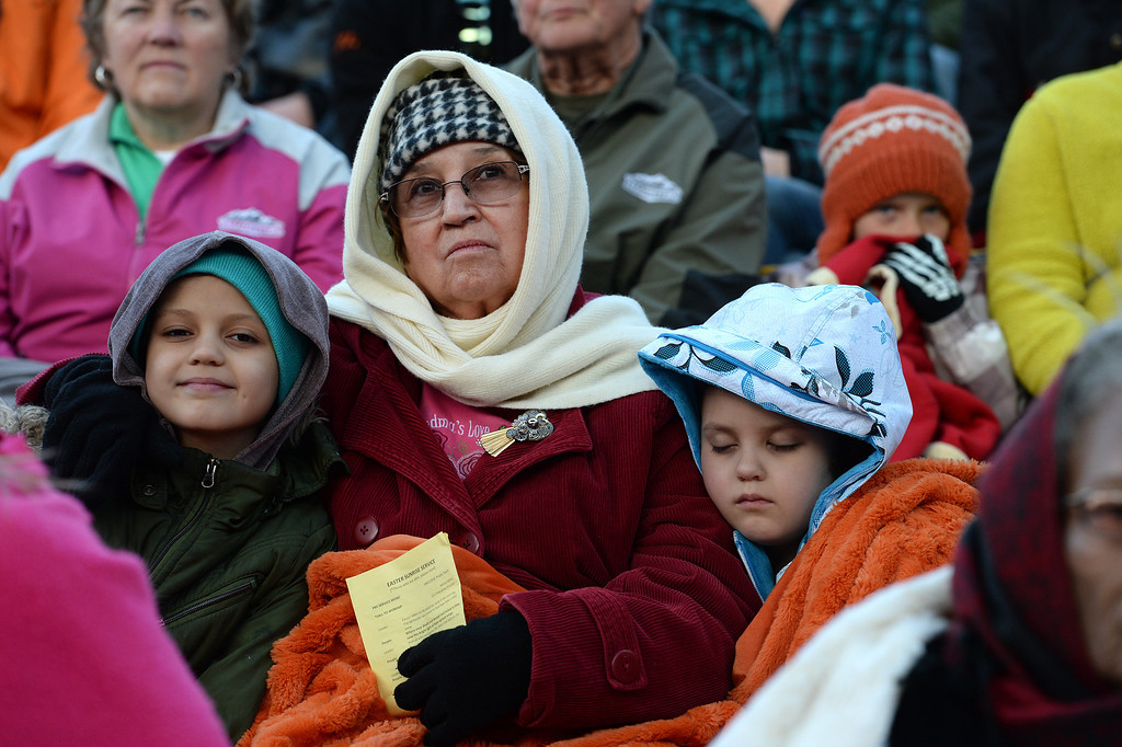 """. Maxine Weaver, middle, and her granddaughters Zoe Weaver, 10, left, and Aspen Weaver, 7, right, listen to the exuberant and passionate sermon given by superintendent Patrick L. Demmer during the 67th annual Easter sunrise service  at Red Rocks Amphitheater in Morrison, Colorado, on April 17, 2014.  Demmer\'s sermon was entitled \""""What are you looking for?\"""".  The popular annual event, which hosts thousands of worshipers, is sponsored by the Colorado Council of Churches.  (Photo By Helen H. Richardson/ The Denver Post)"""
