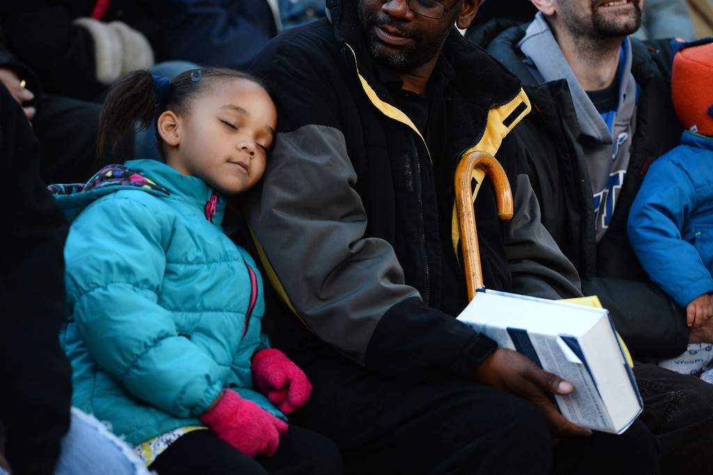 """. Destiny Taylor, 5, left, sleeps on the shoulder of her father Pastor D.P. Taylor, middle, as they, listen to the exuberant and passionate sermon given by superintendent Patrick L. Demmer during the 67th annual Easter sunrise service  at Red Rocks Amphitheater in Morrison, Colorado, on April 17, 2014.  Demmer\'s sermon was entitled \""""What are you looking for?\"""".  The popular annual event, which hosts thousands of worshipers, is sponsored by the Colorado Council of Churches.  (Photo By Helen H. Richardson/ The Denver Post)"""