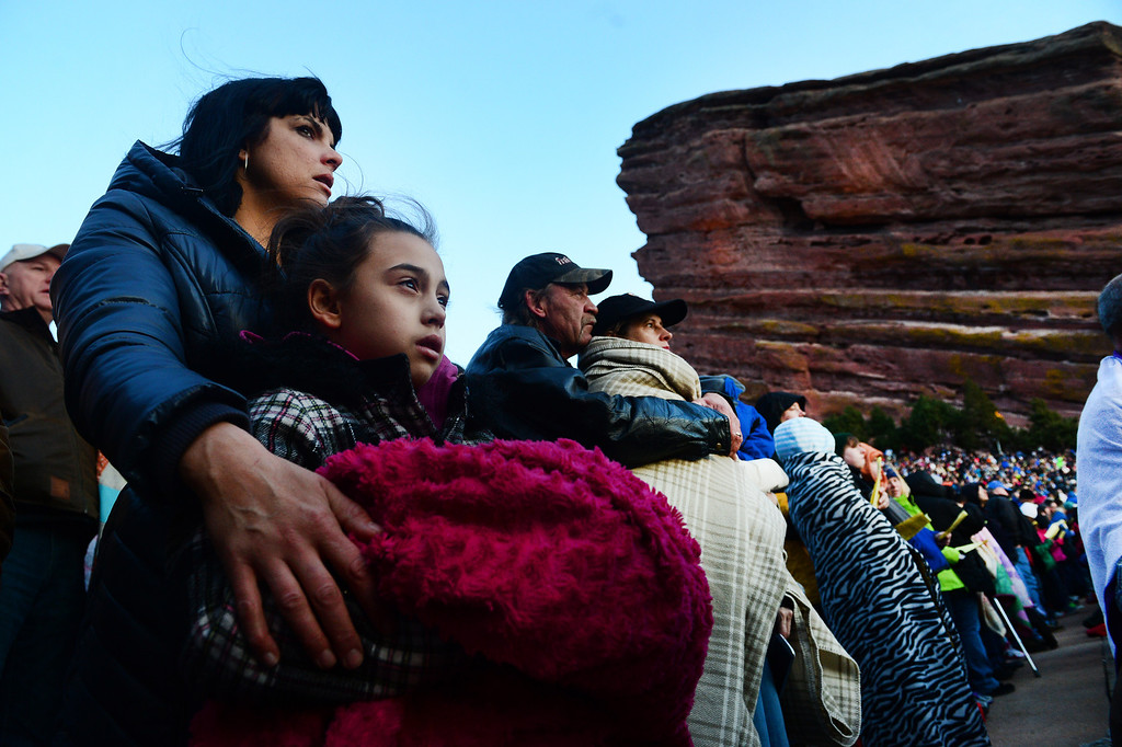 """. Carey Meinert, left, holds her daughter Lucy, 9, as the two enjoy  the 67th annual Easter sunrise service  at Red Rocks Amphitheater in Morrison, Colorado, on April 17, 2014.  Superintendent Patrick L. Demmer gave the sermon which was entitled \""""What are you looking for?\"""".  The popular annual event, which hosts thousands of worshipers, is sponsored by the Colorado Council of Churches.  (Photo By Helen H. Richardson/ The Denver Post)"""