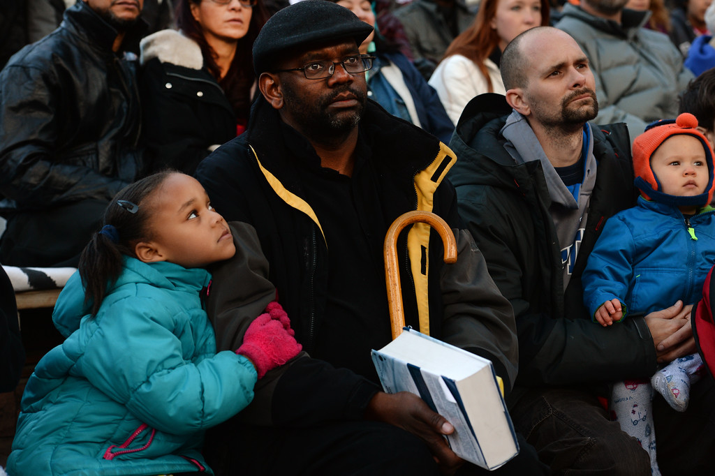 """. Destiny Taylor, 5, left, snuggles next to her  father Pastor D.P. Taylor, middle as they, listen to the  exuberant and passionate sermon given by superintendent Patrick L. Demmer during the 67th annual Easter sunrise service  at Red Rocks Amphitheater in Morrison, Colorado, on April 17, 2014.  Demmer\'s sermon was entitled \""""What are you looking for?\"""".  The popular annual event, which hosts thousands of worshipers, is sponsored by the Colorado Council of Churches.  (Photo By Helen H. Richardson/ The Denver Post)"""